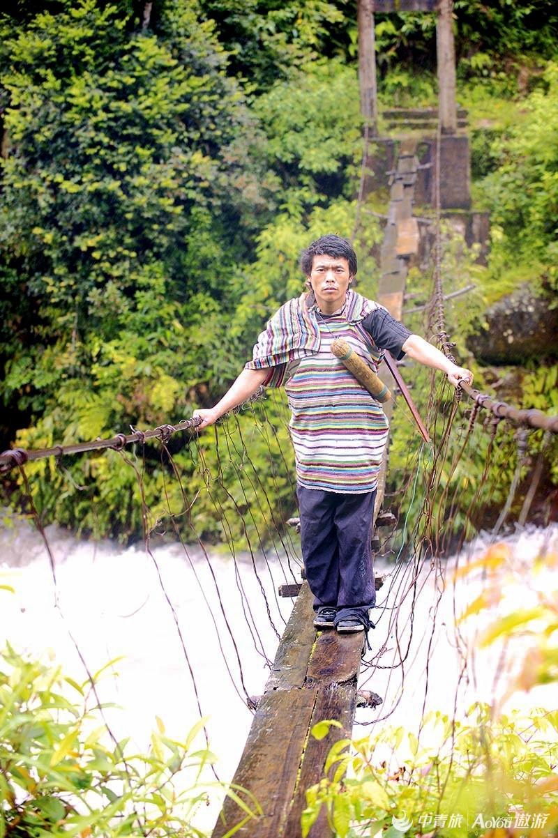 普学华身着独龙毯制成的传统服装,走在普卡娃河的独木桥上。 本报记者 戴焱淼摄.jpg.jpg