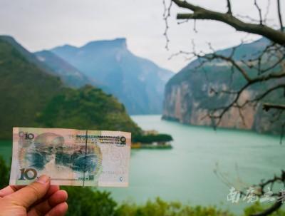 三峡最壮观的瞿塘峡前,很多人举着10元纸币,在看...